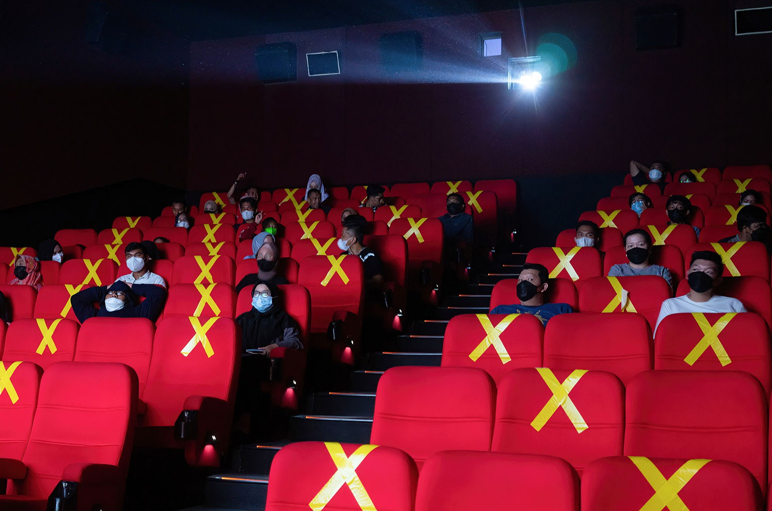 People sitting at a social distance from each other watch a movie at a cinema in 2021