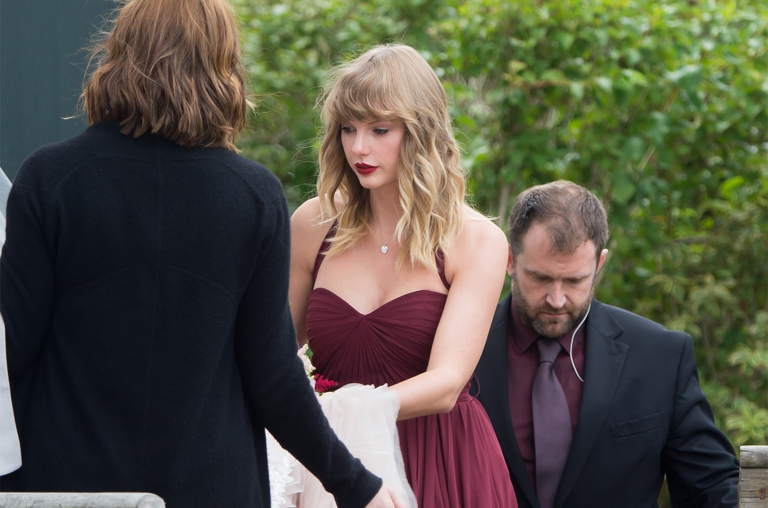 Taylor Swift is seen carrying the back of her best fried Abigail's wedding dress as they arrive at a church in Martha's Vineyard.