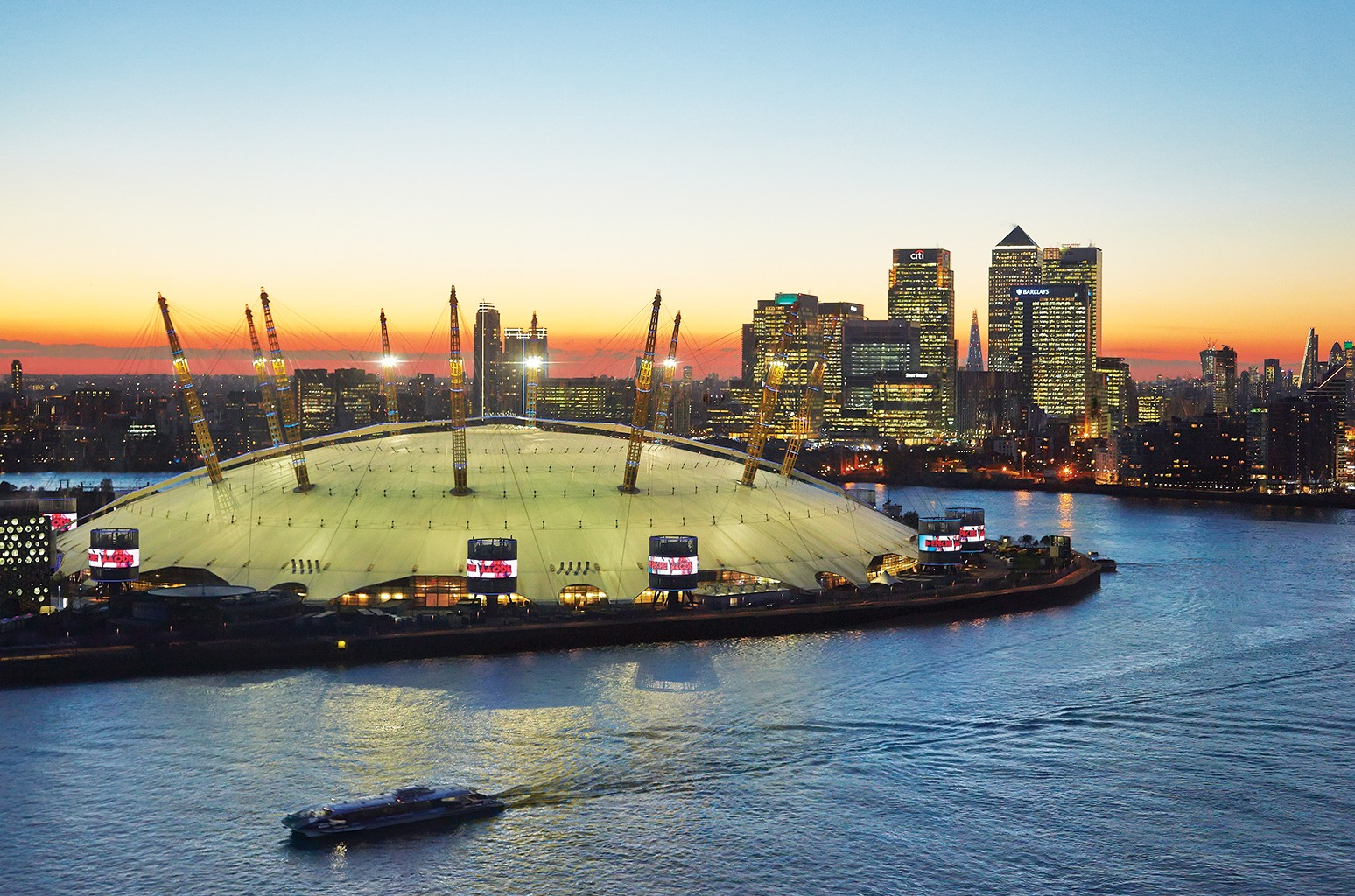 A view from the Emirates Airline of the 02 Arena at sunset with Canary Wharf and the London skyline in the background.