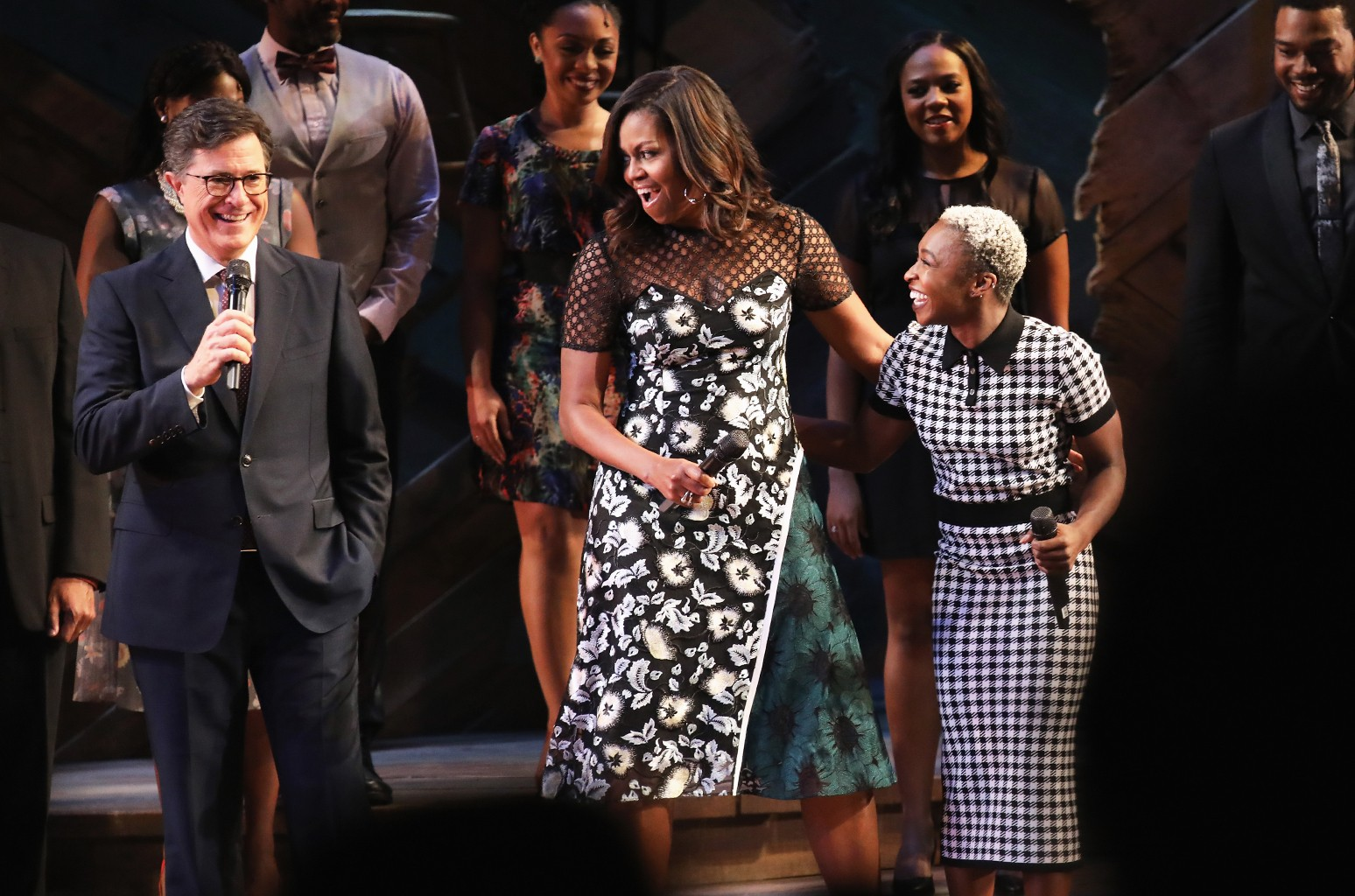 U.S. First Lady Michelle Obama and The Color Purple star Cyntha Erivo listen as Late Show host Stephen Colbert speaks to guests at Broadway's Jacobs Theater on Sept.19, 2016 in New York City.