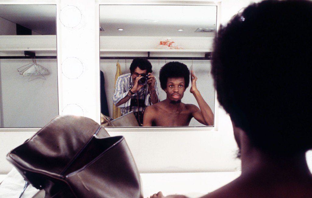 Jim Marshall reflected in the mirror while photographing Verdine White, bass player for Earth, Wind, and Fire, circa 1970