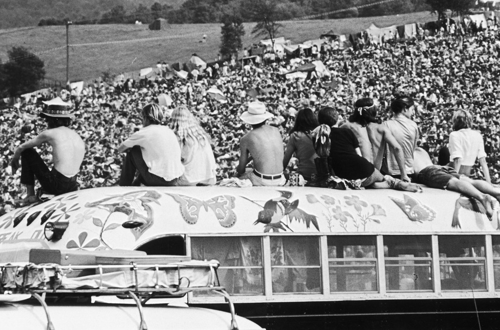 Fans sitting on top of a painted bus at the Woodstock Music Festival, Bethel, New York, 15th-17th August 1969.