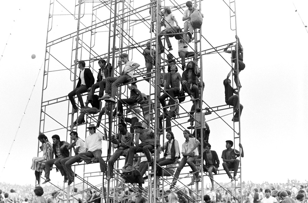 Fans climb a scaffold to get a better view at the Woodstock Music & Art Fair held at Max Yasgur's dairy farm in August, 1969 near White Lake a hamlet of Bethel, New York.
