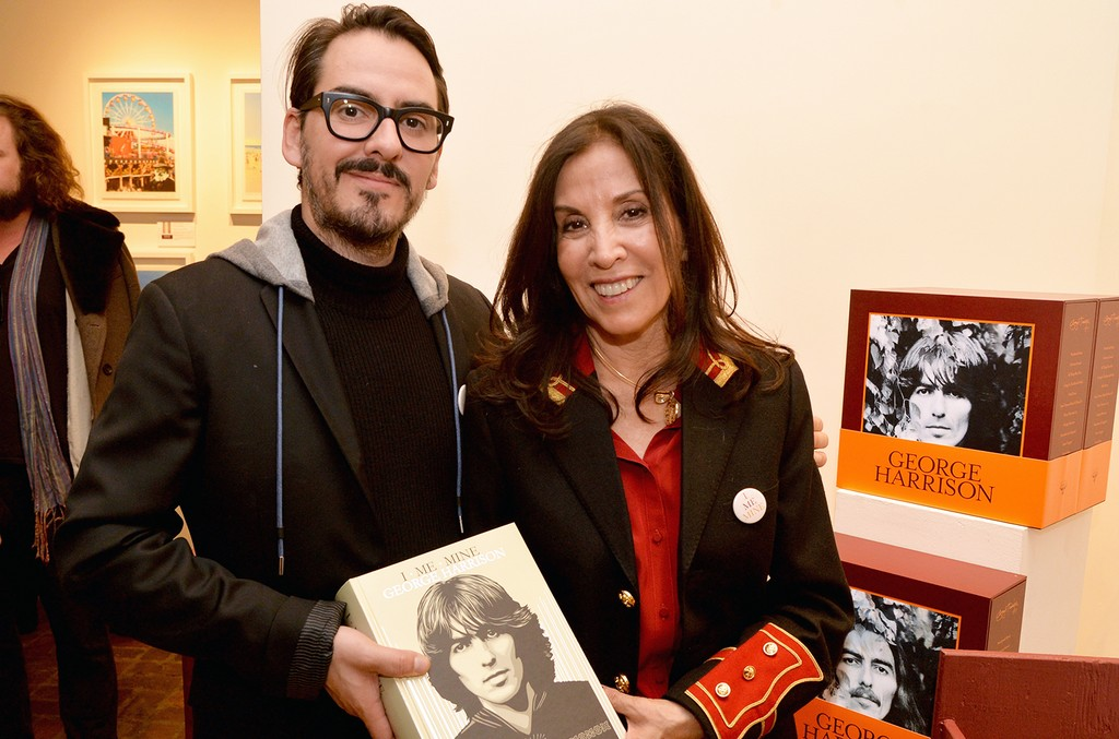 """Dhani Harrison and Olivia Harrison pose with George Harrison's book during the """"I ME MINE"""" George Harrison book launch at Subliminal Projects Gallery on Feb. 25, 2017 in Los Angeles."""