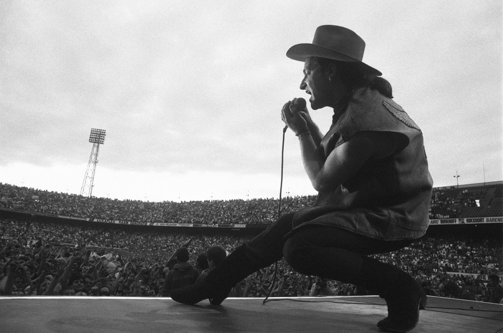 Bono performing live onstage at De Kuip stadium on The Joshua Tree tour, from stage, showing crowds of fans in stadium on July 10, 1987.