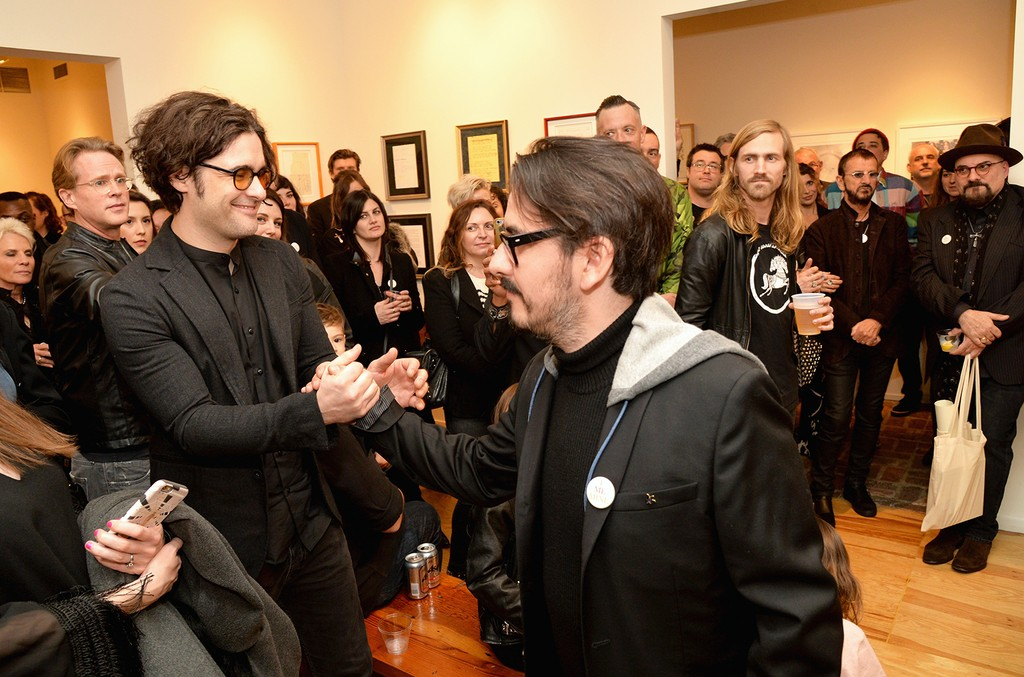 """Robert Levon Been of Black Rebel Motorcyle Club and Dhani Harrison shake hands during the """"I ME MINE"""" George Harrison book launch at Subliminal Projects Gallery on Feb. 25, 2017 in Los Angeles."""
