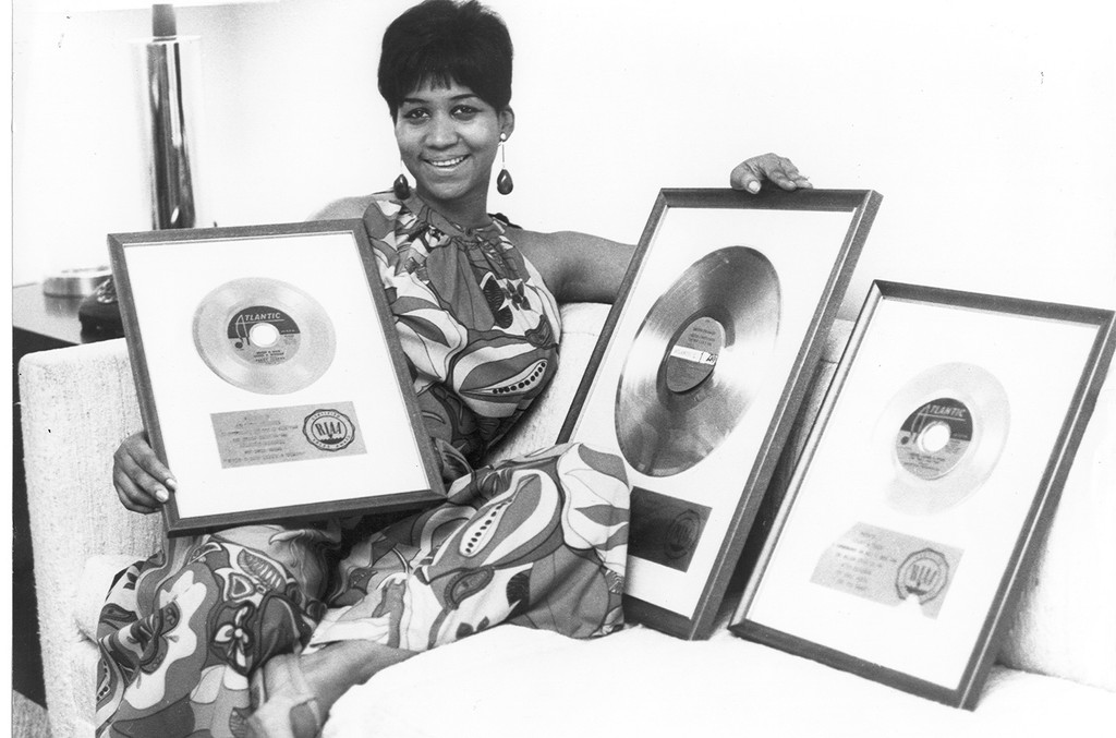Aretha Franklin poses for a portrait with three plaques of records celebrating milestones in sales in circa 1969.