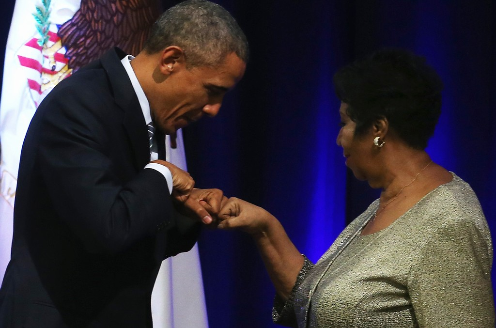 President Barack Obama fist bumps with singer Aretha Franklin who sung during a farwell ceremony for Attorney General Eric Holder at the Justice Department February 27, 2015 in Washington, DC.