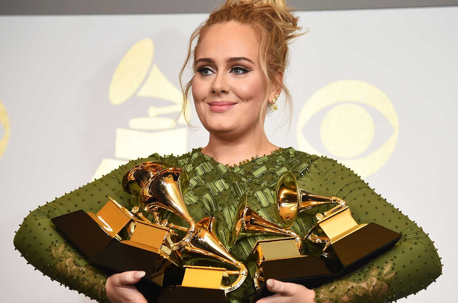 """Adele poses in the press room with her trophies, including the top two Grammys of Album and Record of the Year for her blockbuster hit """"Hello"""" and the album """"25"""", during the 59th Annual Grammy music Awards on Feb. 12, 2017 in Los Angeles."""