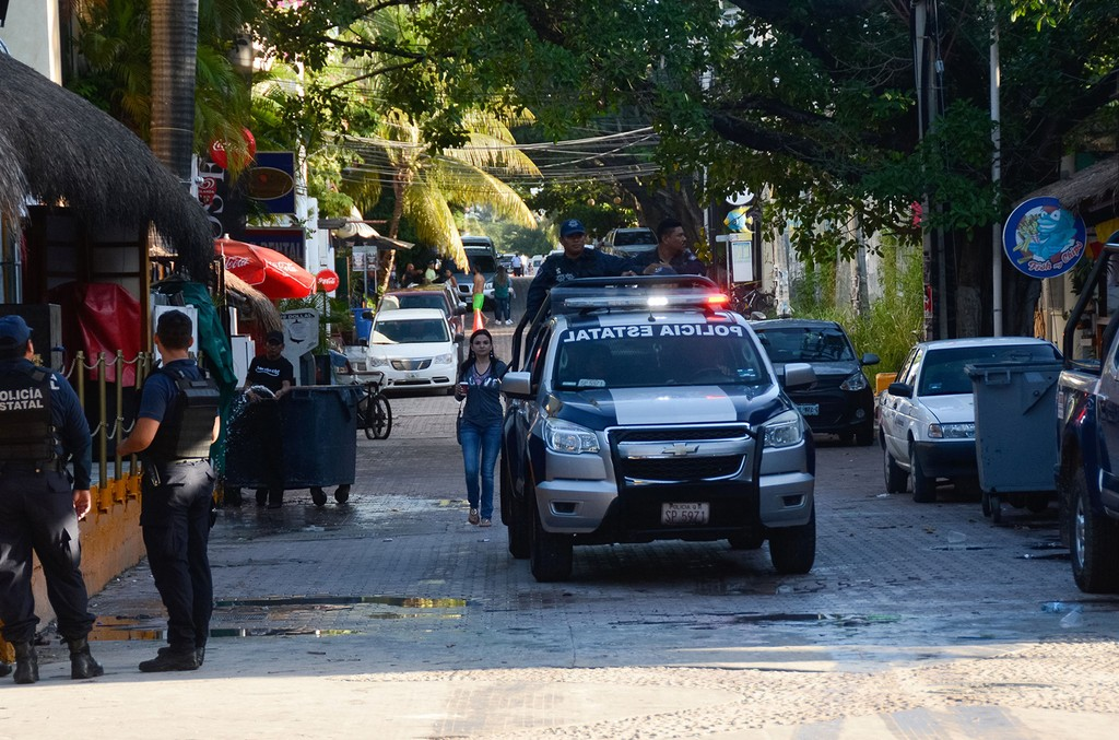 Mexican police agents patrol near a nightclub in Playa del Carmen, Quintana Roo state, Mexico where 5 people were killed, three of them foreigners, during a music festival on Jan. 16, 2017.