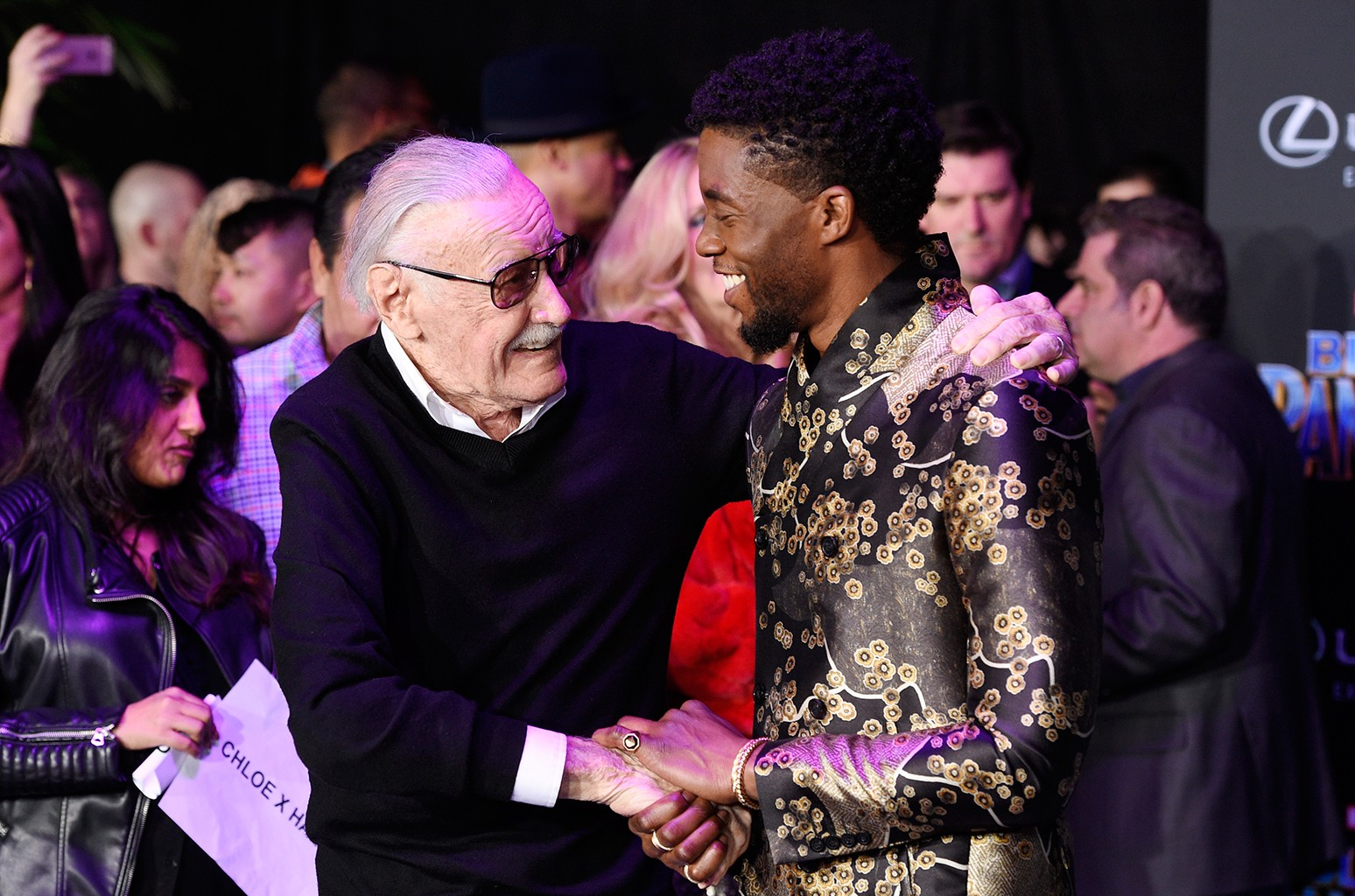"Comic book creator Stan Lee, left, shakes hands with Chadwick Boseman, star of ""Black Panther,"" at the premiere of the film at The Dolby Theatre on Jan. 29, 2018 in Los Angeles."