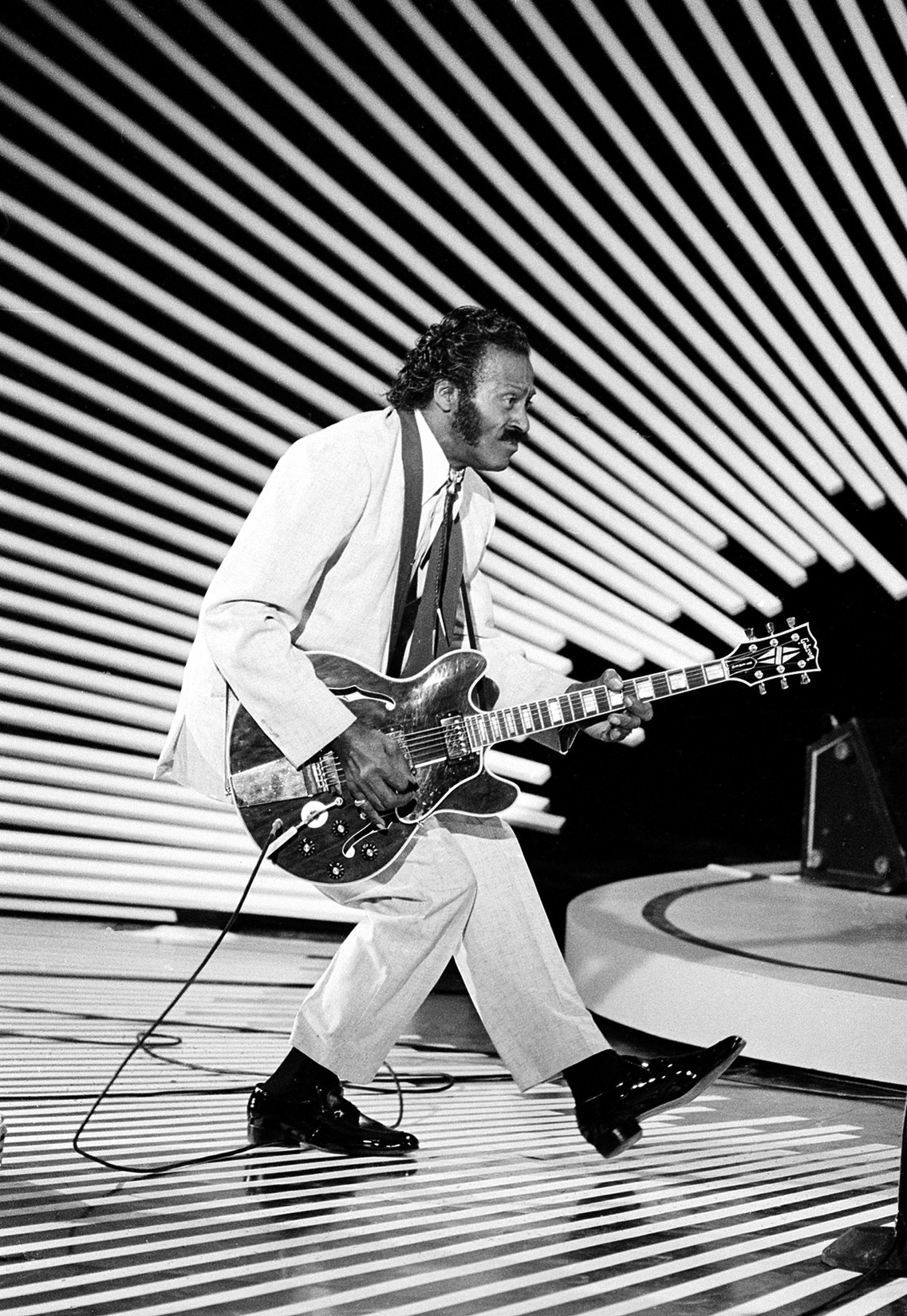"""Chuck Berry performs his """"duck walk"""" on stage as he plays his guitar on April 4, 1980."""