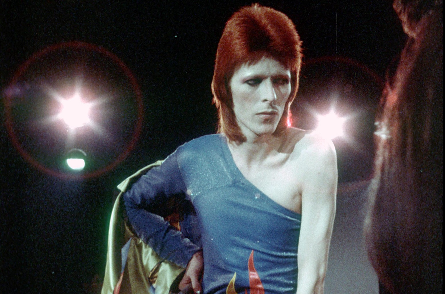 """David Bowie performs onstage during his """"Ziggy Stardust"""" era in 1973."""
