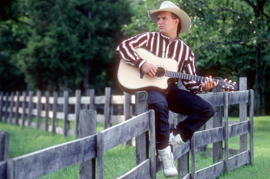 Garth Brooks poses for a portrait session on a fence wearing a cowboy hat and playing a Takamine acoustic guitar on Aug. 15, 1991 in Nashville.