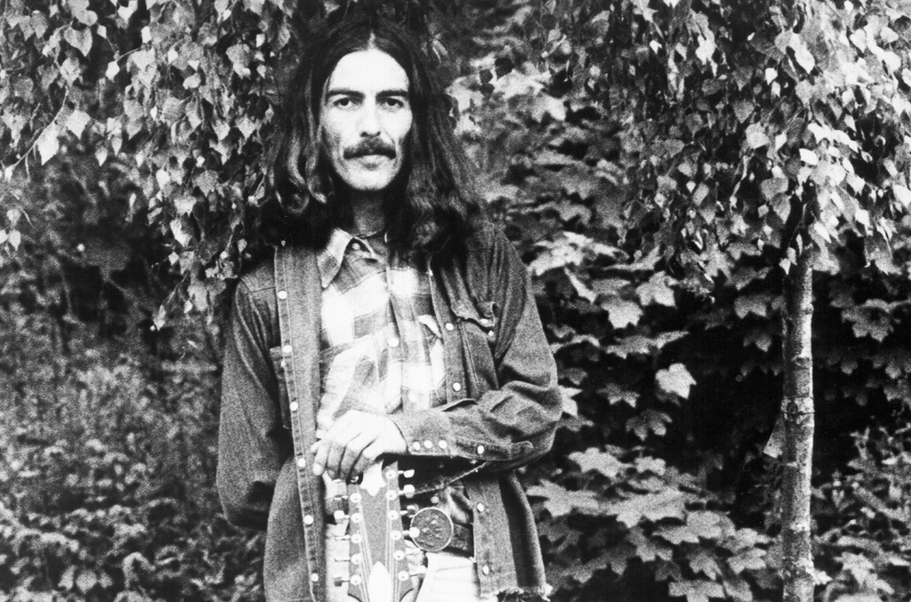 George Harrison poses for a portrait with an acoustic guitar in circa 1974.