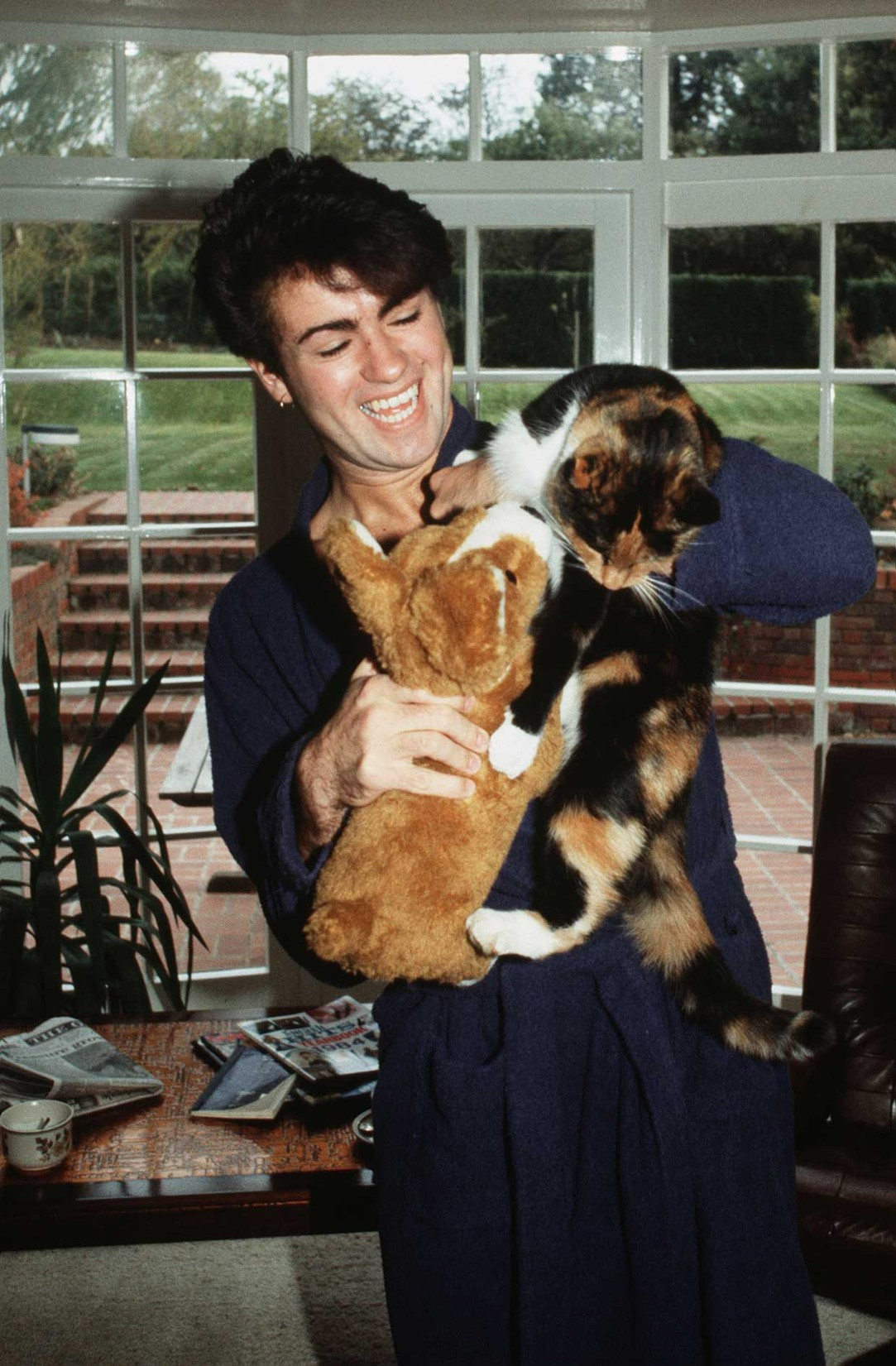 George Michael poses at home with his cat after losing his voice and being forced to cancel a number of live shows in London in 1980.