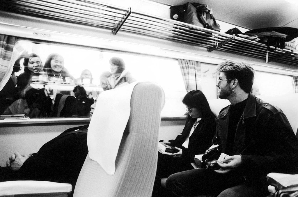 George Michael with girlfriend Kathy Yeung on a train looking at fans through the window in Japan in March, 1988.