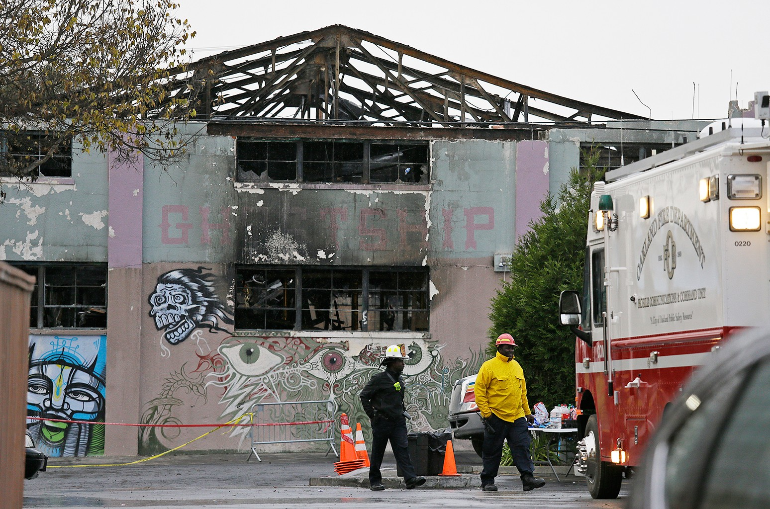 Oakland fire officials walk past the remains of the Ghost Ship warehouse damaged from a deadly fire in Oakland, Calif.