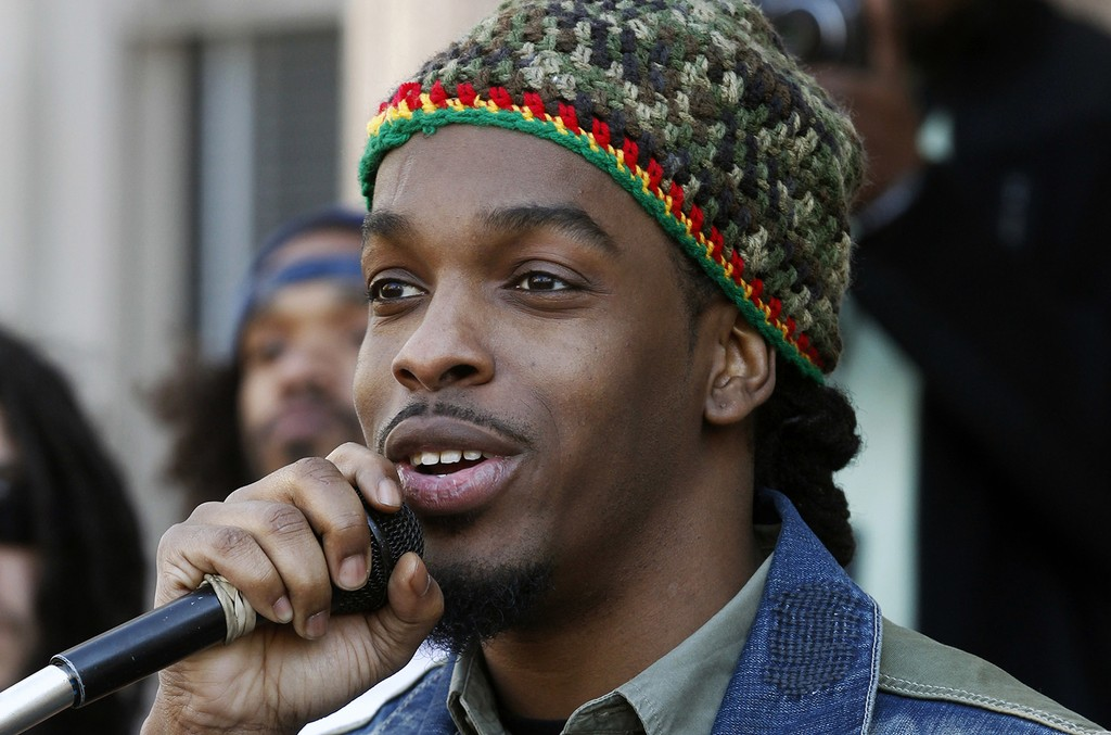 Jawara McIntosh, son of Peter Tosh, sings a song as he stands with a large gathering in front of the New Jersey Statehouse on April 20, 2014 in Trenton, N.J.