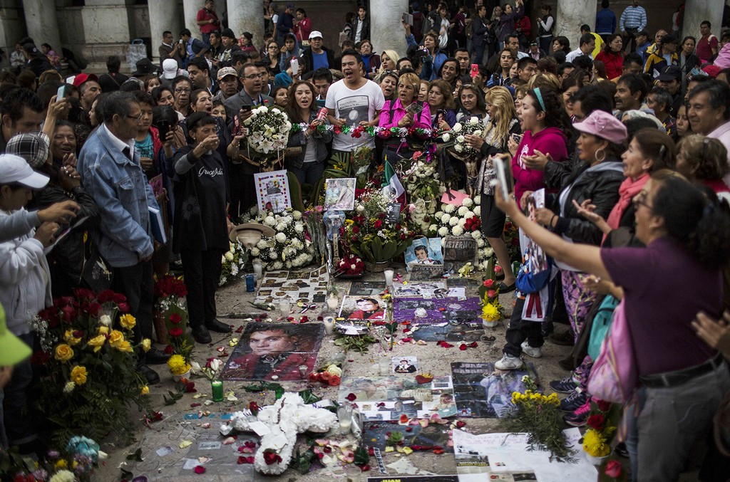 People sing next to an altar of Mexican songwriter and singer Juan Gabriel is seen next to the Bellas Artes Palace in Mexico City, on Sept. 4, 2016 in Mexico City, Mexico.