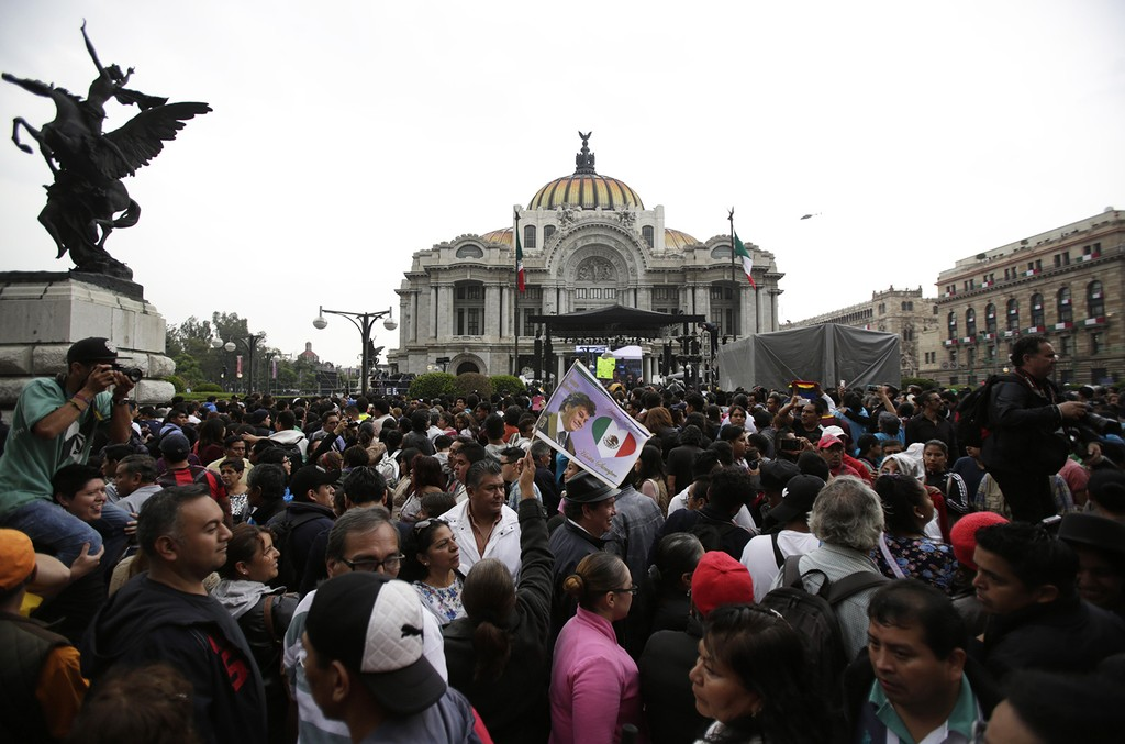 People stand outside the Palacio de Bellas Artes during the Memorial of Mexican singer Juan Gabriel on Sept. 5, 2016 in Mexico City, Mexico.