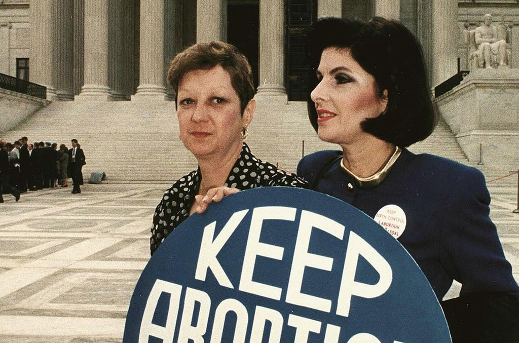 """Norma McCorvey (L) formally known as """"Jane Roe"""", as she holds a pro-choice sign with former attorney Gloria Allred (R) in front of the US Supreme Court building April 26, 1989."""