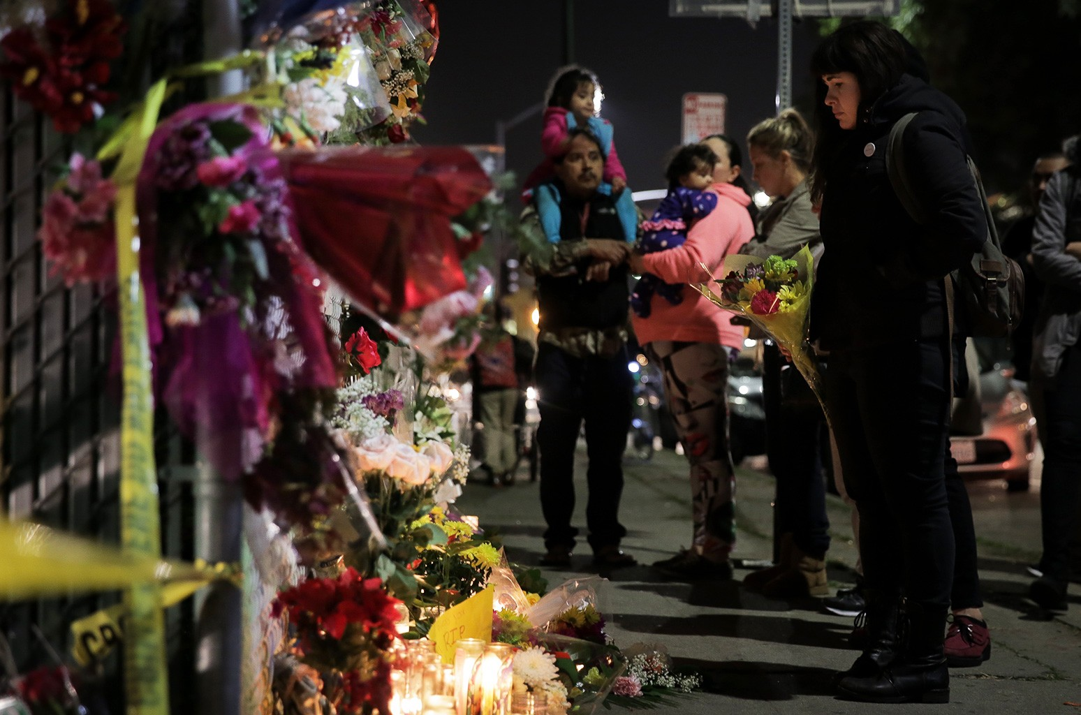 People look at a memorial near the site of a warehouse fire that has claimed the lives of at least thirty-six people on Dec. 5, 2016 in Oakland, Calif.