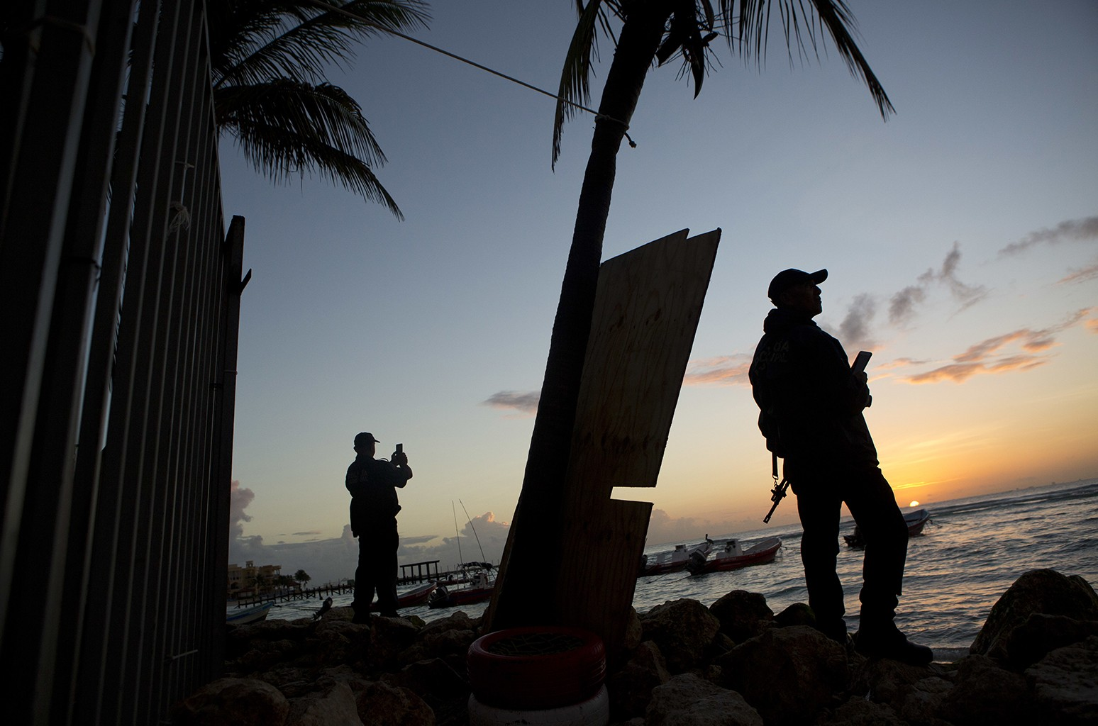 Municipal police watch the sunrise as they stand guard on the beach in front of the Blue Parrot club, a day after a deadly early morning shooting, in Playa del Carmen, Mexico on Jan. 17, 2017.