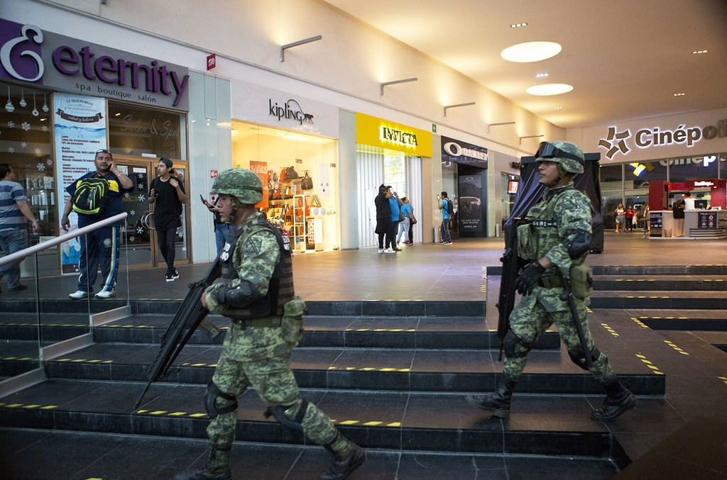 Soldiers walk inside Plaza Las Americas mall following reports of gunfire in Cancun, Mexico on Jan. 17, 2017.