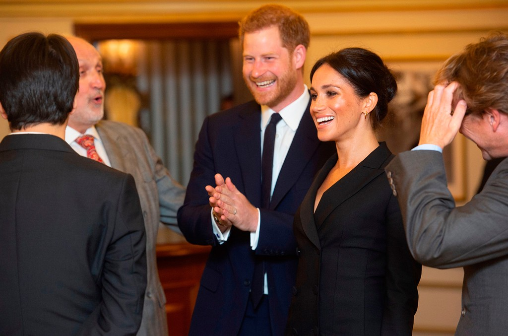 Britain's Prince Harry, Duke of Sussex (C), and Britain's Meghan, Duchess of Sussex