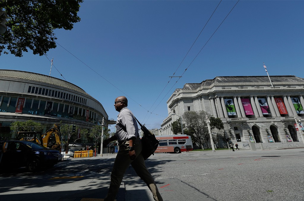 A man walks along Van Ness Avenue across the street from Louise M. Davies Symphony Hall, left, and War Memorial Opera House in San Francisco.