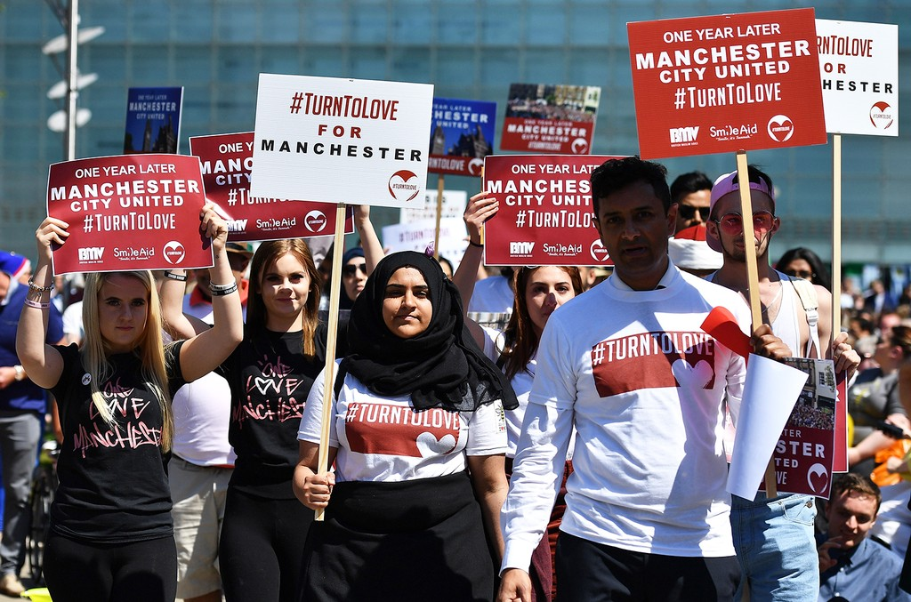 Cross faith group #TurnToLove walk outside The Manchester Arena National Service of Commemoration at Manchester Cathedral on May 22, 2018 in Manchester, England.