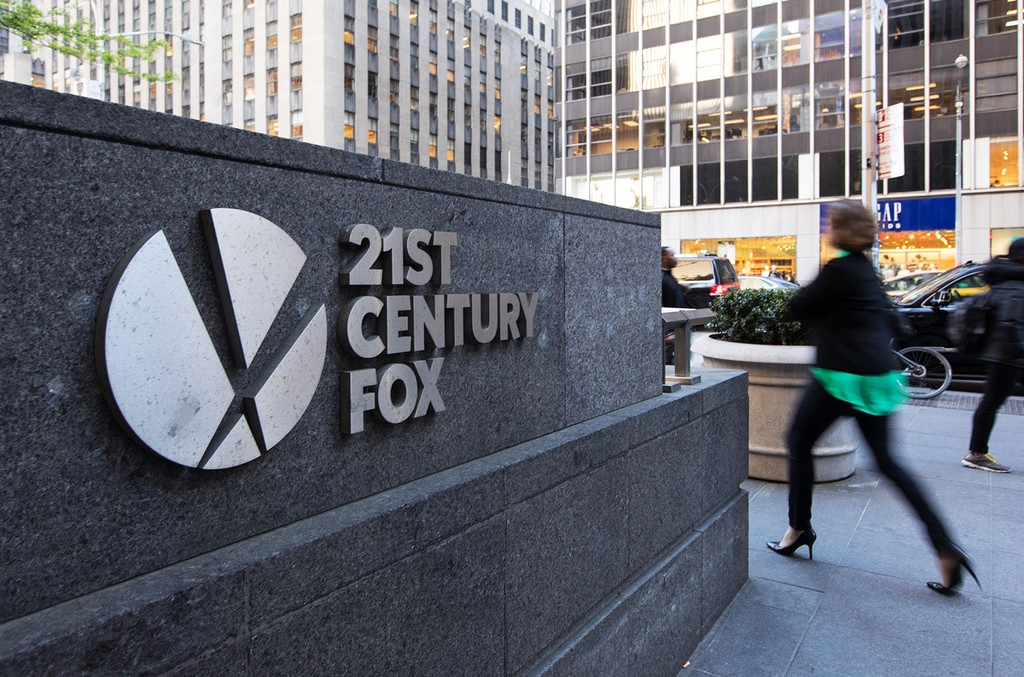 Pedestrians pass in front of signage outside Twenty-First Century Fox Inc. headquarters in New York on May 3, 2017.