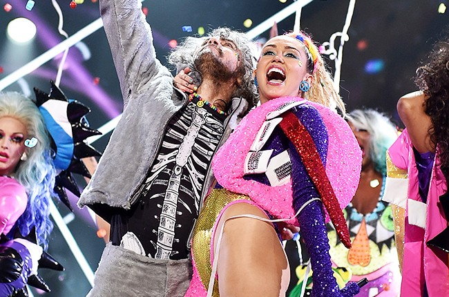 Wayne Coyne of The Flaming Lips (L) and host Miley Cyrus