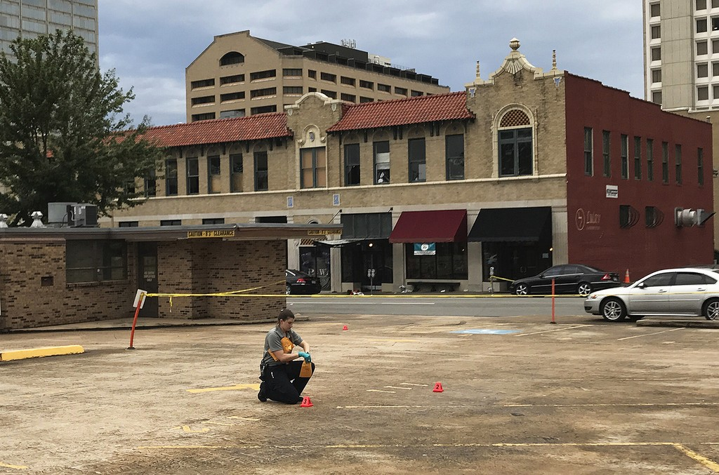 An investigator collects evidence near an Arkansas nightclub where police say multiple people were shot on July 1, 2017 in Little Rock, Ark.