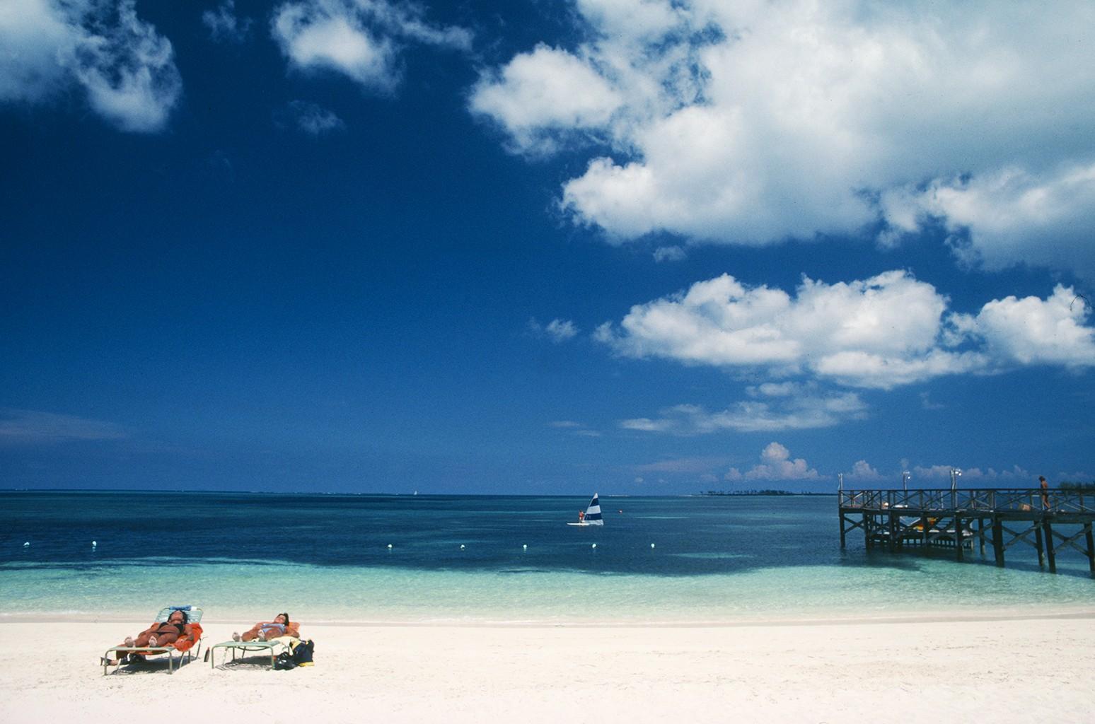 Two women sunbathing on a beach in the Bahamas.