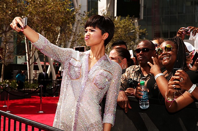 Zendaya poses on the red carpet for a selfie photo with fans at the 2015 BET Awards