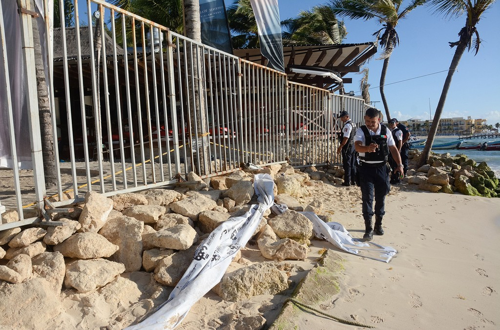 Mexican police agents, investigate at a nightclub near the beach in Playa del Carmen, Quintana Roo state, Mexico where 5 people were killed, three of them foreigners, during a music festival on Jan. 16, 2017.