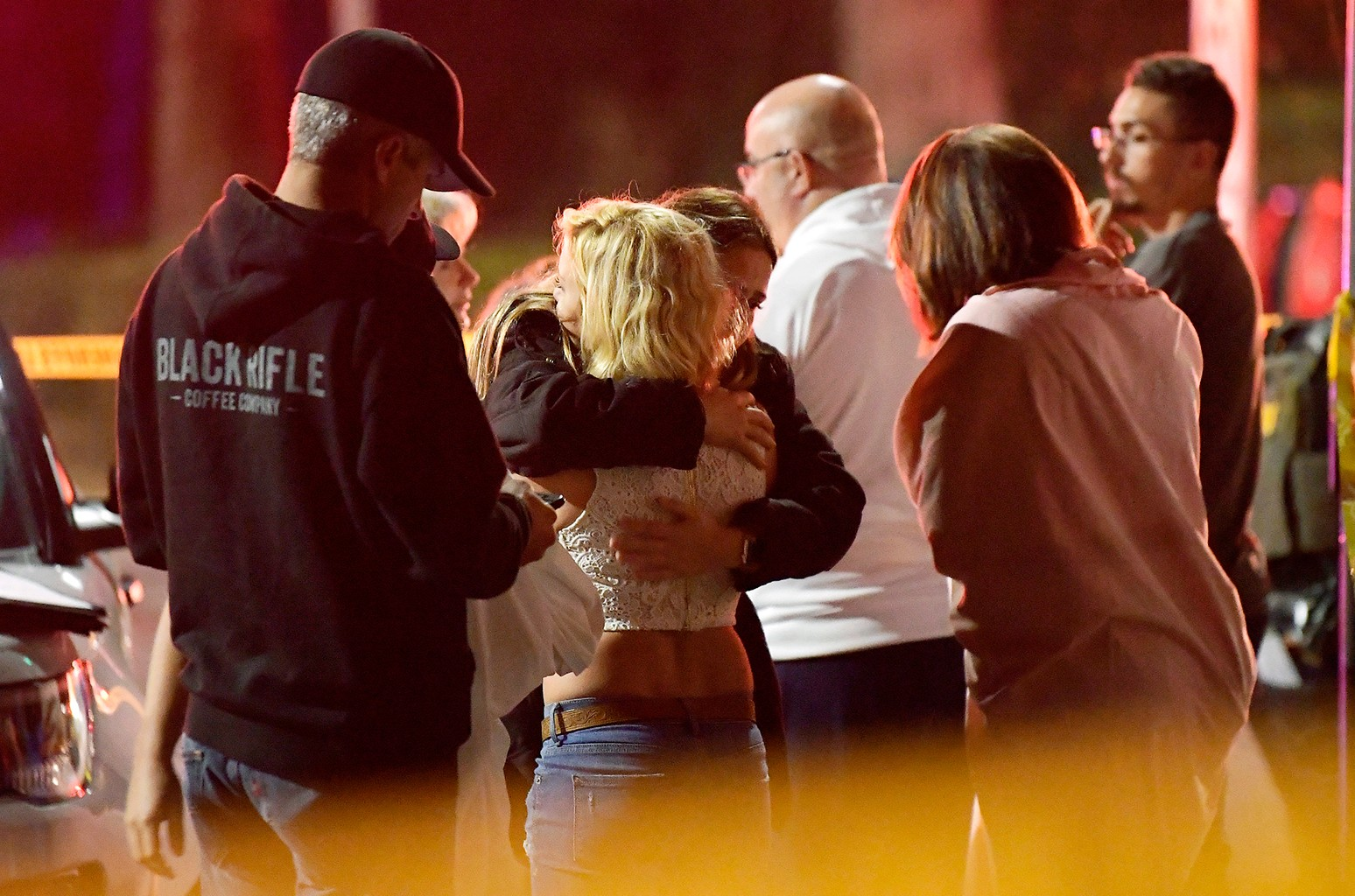 """People comfort each other as they stand near the scene Thursday, Nov. 8, 2018, in Thousand Oaks, Calif., where a gunman opened fire Wednesday inside a country dance bar crowded with hundreds of people on """"college night,"""" wounding multiple people including"""