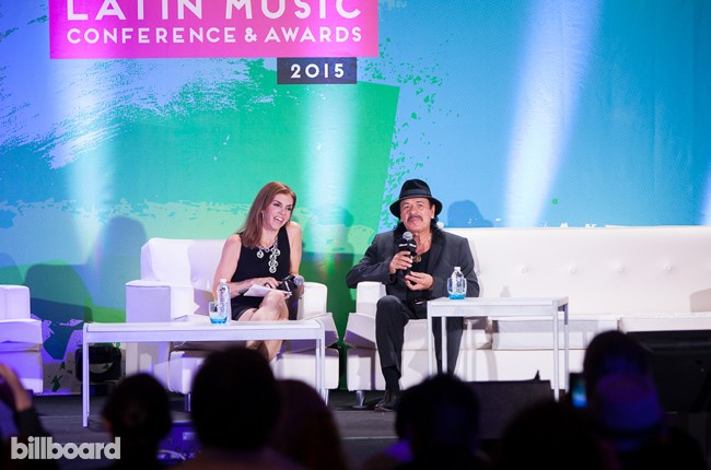 """Carlos Santana onstage at the """"Legends"""" panel with Billboard editor Leila Cobo at the 2015 Billboard Latin Conference in Miami on April 29, 2015."""