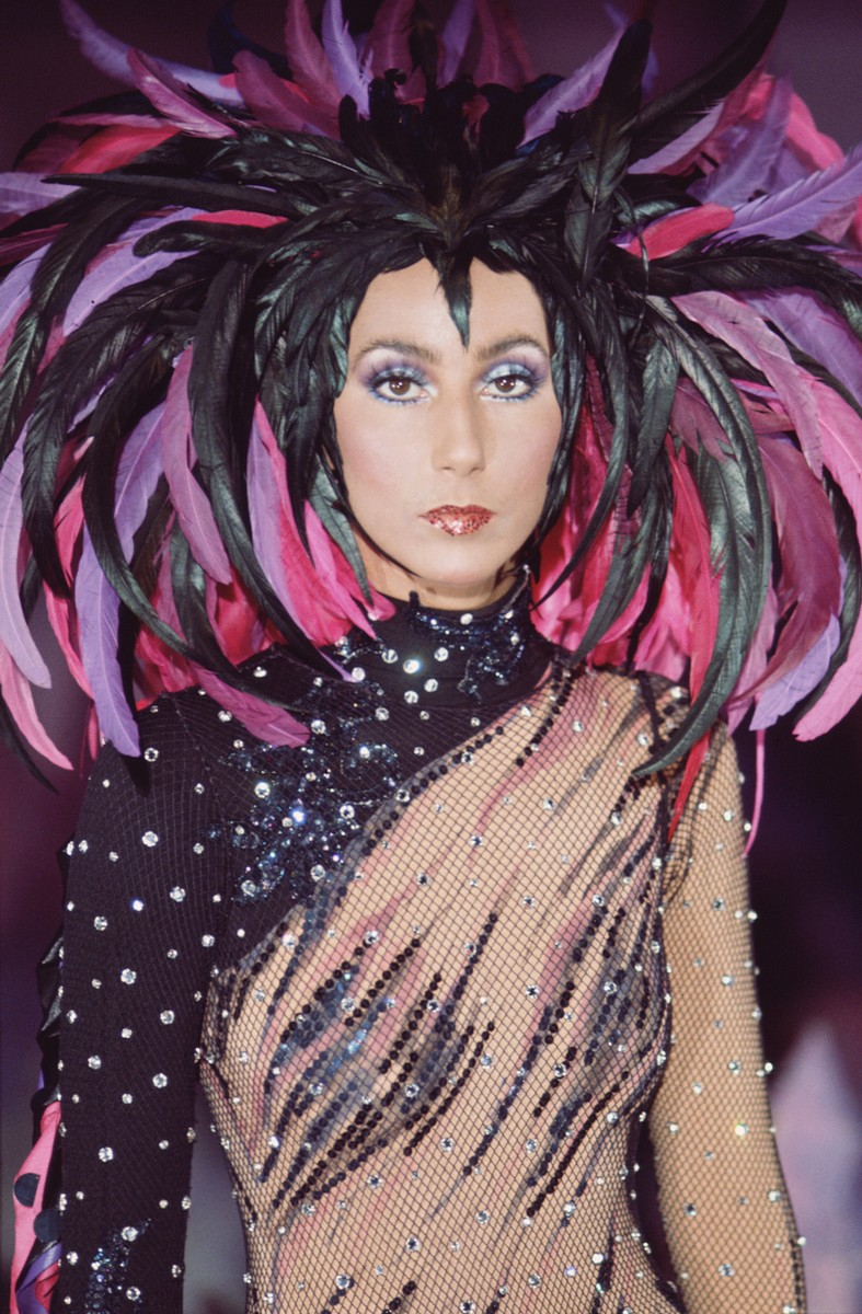 Cher in a semi-transparent outfit with a feathered headdress for the television variety show 'The Sonny and Cher Comedy Hour' in 1972. (Photo by CBS Photo Archive/Getty Images)