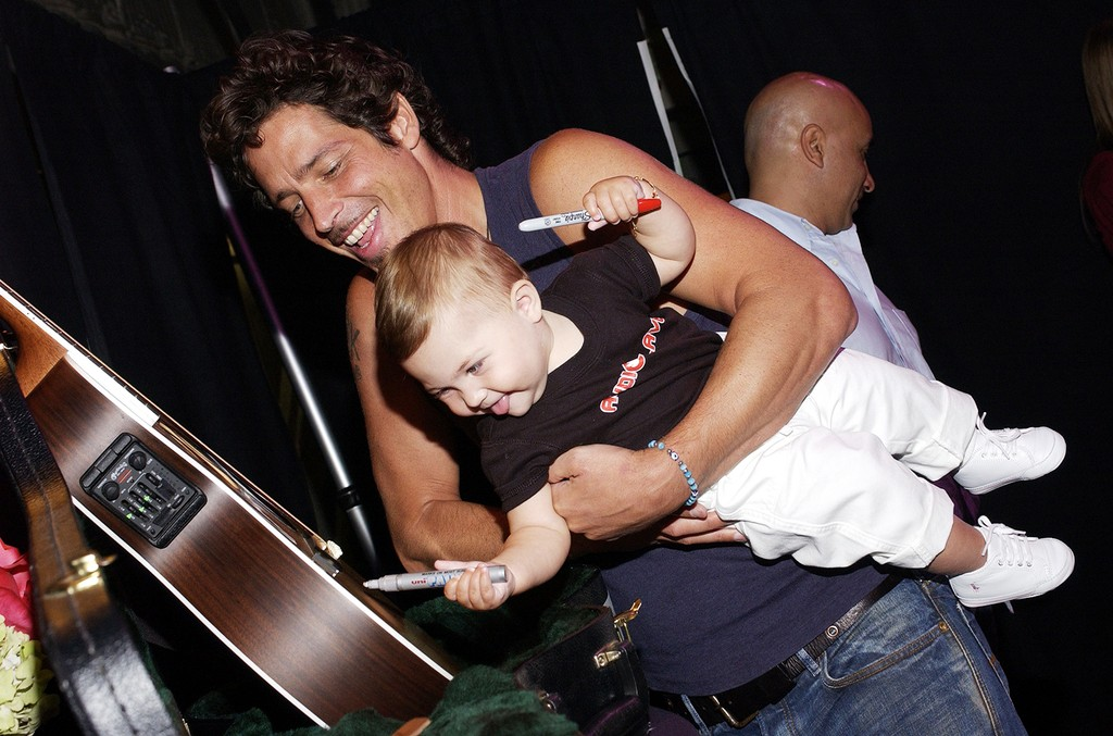 "Chris Cornell of Audioslave and his daughter Toni sign a guitar donated by the band at the ""ReAct Now: Music & Relief"" benefit concert at Paramount Studios on Sept. 10, 2005 in Hollywood, Calif."
