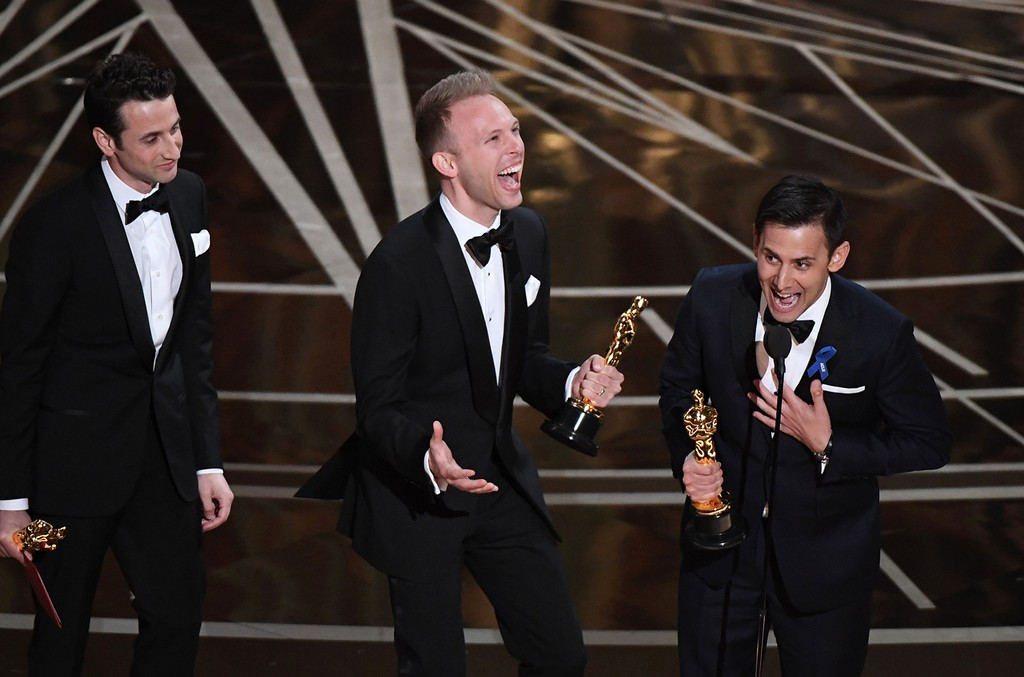 """Composers Justin Hurwitz, Justin Paul and Benj Pasek celebrate on stage after they won the Best Original Song award for """"City of Stars - La La Land"""" at the 89th Oscars on Feb. 26, 2017 in Hollywood, Calif."""