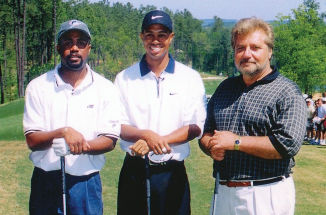 Darius Rucker, Tiger Woods and Martin Bandier on a golf course.