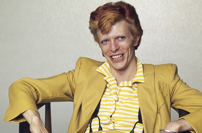 David Bowie with dyed red hair and a mustard yellow suit, circa 1974.