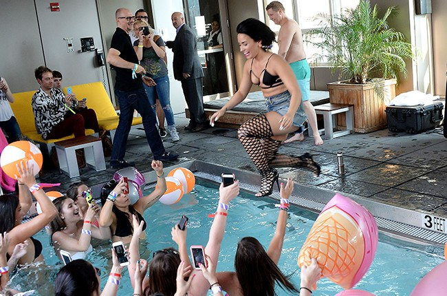 """Demi Lovato jumps into the pool after performing her new single, """"Cool for the Summer,"""" with Z100 at Gansevoort Park Avenue on July 1, 2015 in New York City."""