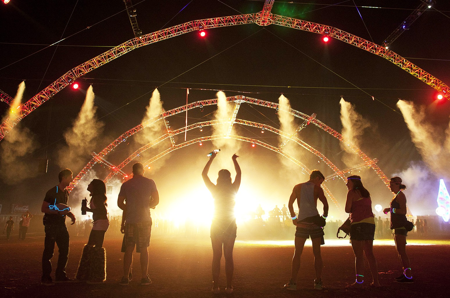Carnival goers dance near the back of the crowd at one of six stages during the third day of the Electric Daisy Carnival in Las Vegas.