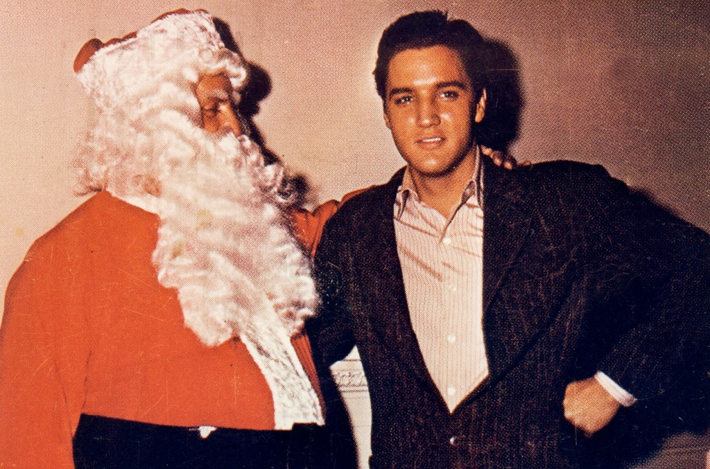 Elvis Presley poses with Colonel Tom Parker dressed as Santa Claus in this Christmas card circa 1965.