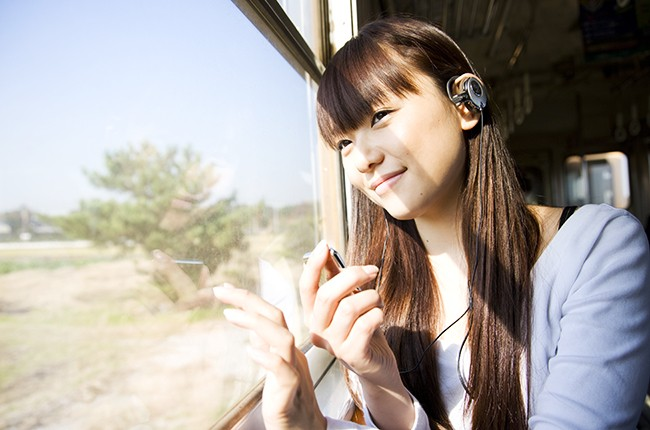 A girl listening to the music on a train.