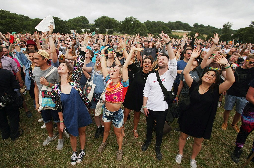 The crowd cheer during an unofficial record-breaking attempt at creating the biggest human peace sign ever, in the Stone Circle field at the Glastonbury Festival at Worthy Farm in Pilton, Somerset.